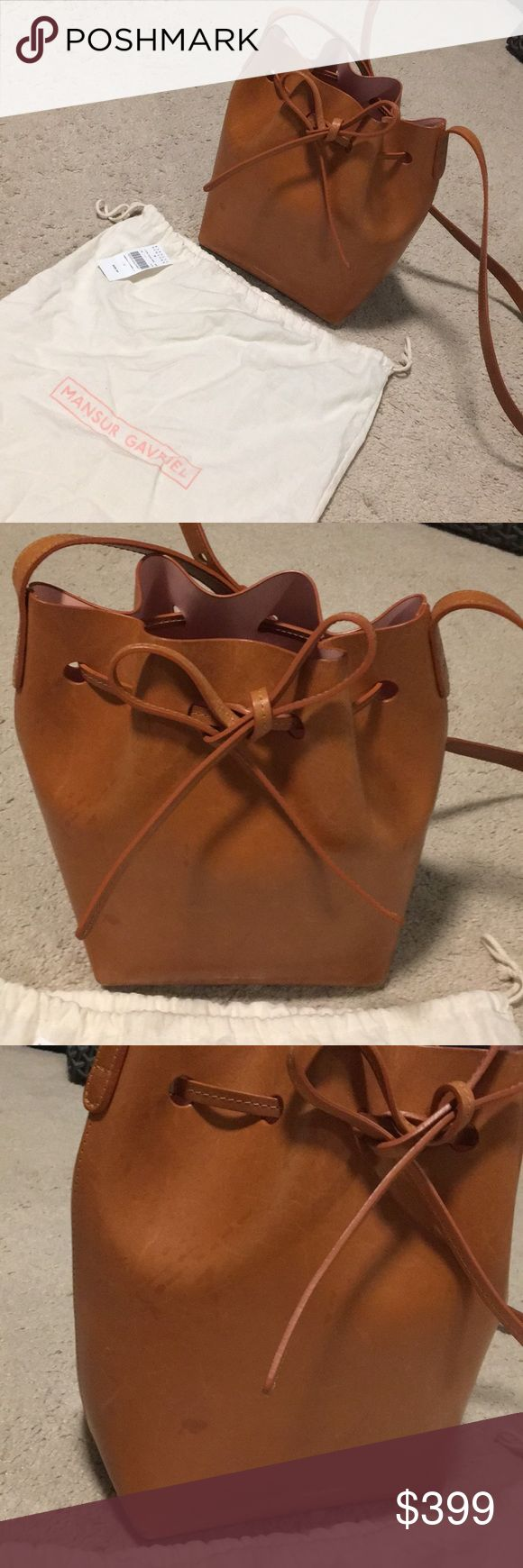 Mansur Gavriel Mini Tan Bucket Bag ✨ $325 on 🅿️ Worn a few times. Small scratches as pictures but it actually adds a bit of character to the bag, and Mansur Gavriel themselves say that each bag and the unique wear and tear it gets is meant to 'tell a story'.  The cammellotan colour really compliments the nude-pinkrosa of the lining. Comes with dust bag and tags. The mini is the medium sized bag! 💗 325 over ♈️enmo or 🅿️🅿️ Mansur Gavriel Bags Crossbody Bags