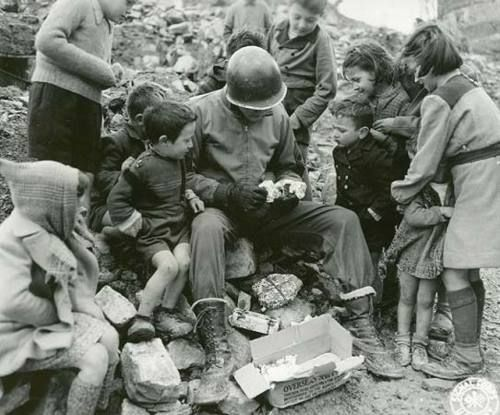 An American soldier sharing his Christmas package with children somewhere in Italy