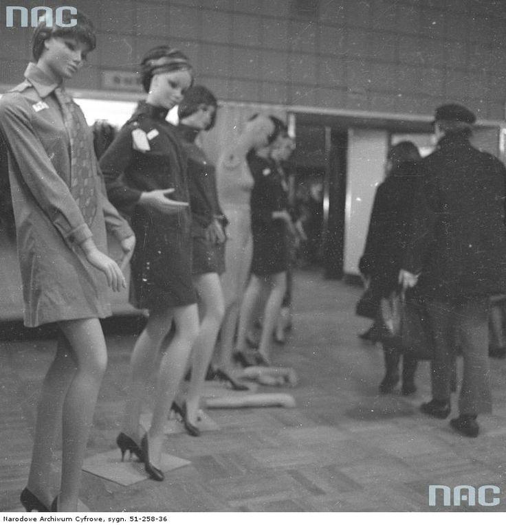 """Klienci oglądający odzież damską z kolekcji """"Przekroju"""" w salonie mody na VI piętrze. Widoczne manekiny ustawione w rzędzie."""