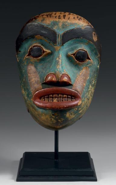 Important MASQUE portrait chamanique en bois sculpté polychrome. Visage à fond bleu aux traits naturalistes, les yeux globuleux et bridés, bouche ovale rouge montant la dentition. Couleurs délavées, reprenant une affiliation shamanique. HAIDA/ KWAKIULT (Colombie Britanique) Vers 1880 - 1900 Hauteur 28 cm Ce masque est à rapprocher d'une série de trois masques plus anciens collectés entre 1824 et 1934 conservé au British Museum, au Peabody Museum et au Smithsonian Institute