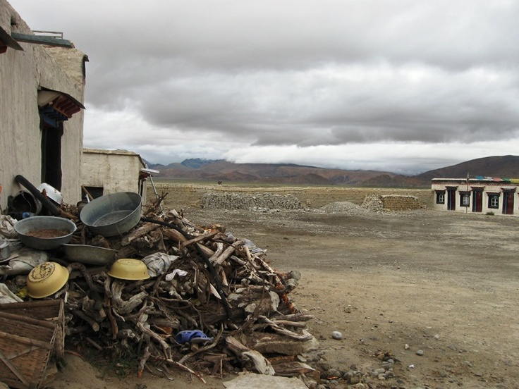 Guest house at Lao Tingri - tins, cans and firewood in the foreground, with the unbroken chain of the Himalayas in the distance.