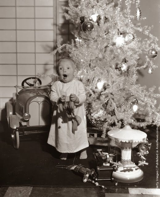 One-year-old Paramount child star Baby LeRoy plays with his new toys under the Christmas tree. (Photo by Hulton Archive/Getty Images). 1933.