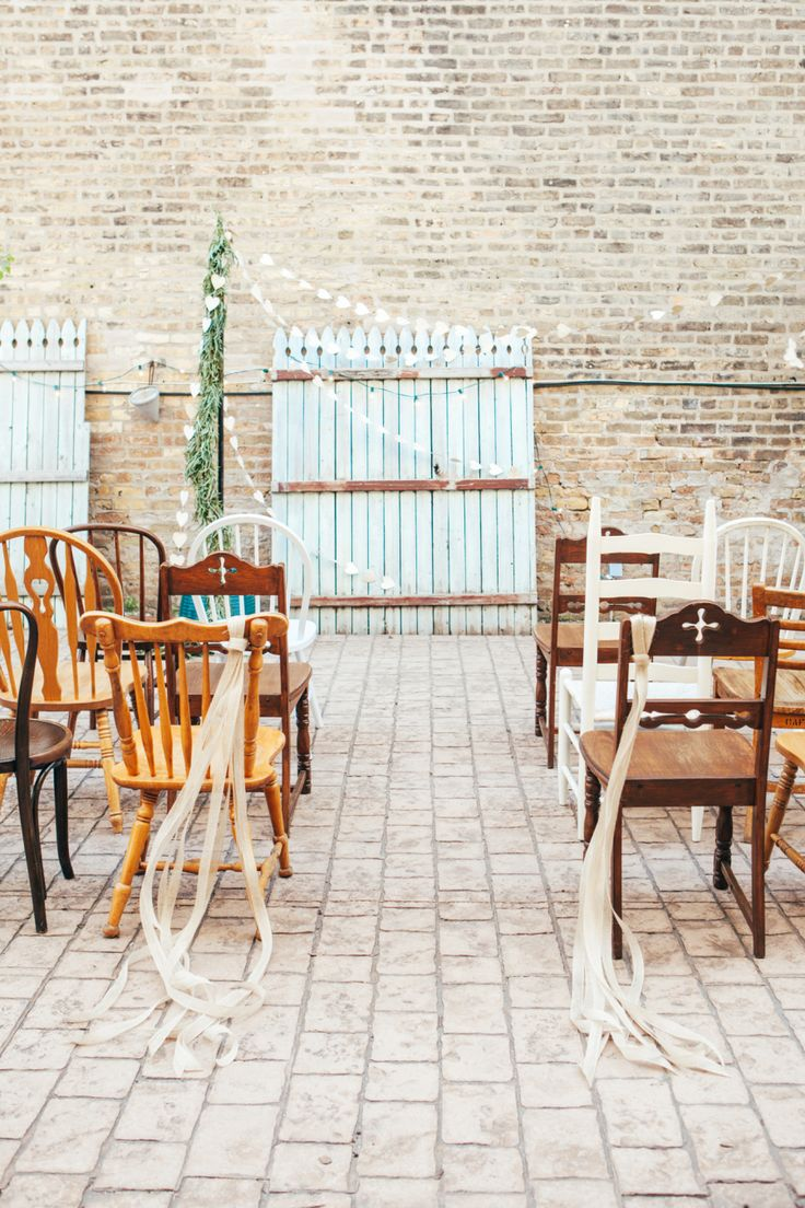 {{The outdoor scene for a spring wedding editorial at Lovely Kitchen and Cafe in Chicago: varied rustic chairs, wisping ribbons, strands of paper hearts, and a soft blue backdrop, featured in Style Me Pretty.}} Photography and concept by Studio Finch http://studiofinch.com/    Flowers by Pollen, pollenfloraldesign.com
