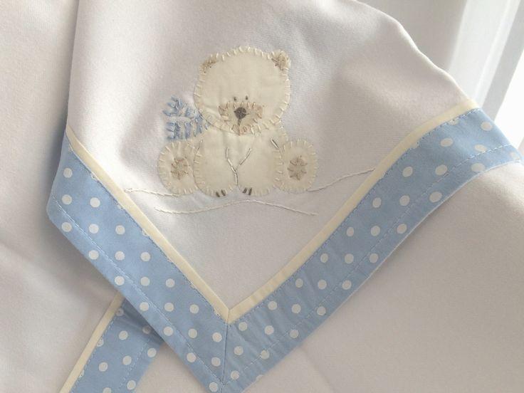 O Cueiro de Flanela é bordado à mão com desenho do Urso Polar e detalhes em azul. As bordas são de tecido azul estampado com poás marfim, tema da coleção. Totalmente em algodão, mede 78 x 78 centímetros.