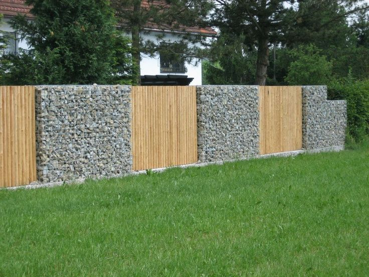 gabion fence - use pallet wood panels (If gabions are thick, wood panels can be on outer edge of gabion, so this would be the neighbor's view, and inside can make seating in the recessed wood areas)