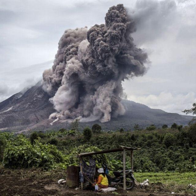Un agricoltore nei campi circostanti il Monte Sinabung in eruzione, visto dal villaggio di Tiga Kicat, presso Sukanalu, sull'isola di Sumatra, in Indonesia