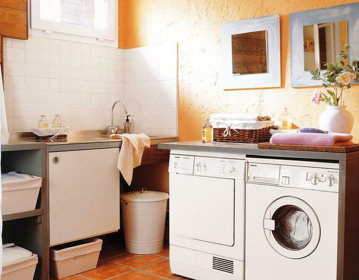"""La parte de lavado se organiza en """"L"""", con el fregadero y la pared alicatada con azulejos, en un lado; y la lavadora y secadora en el otro, con pared pintada en color albero. Dos muebles de madera a medida albergan la lavadora y la secadora, y un práctico fregadero."""
