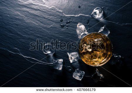Glass of whiskey with ice cubes on dark table