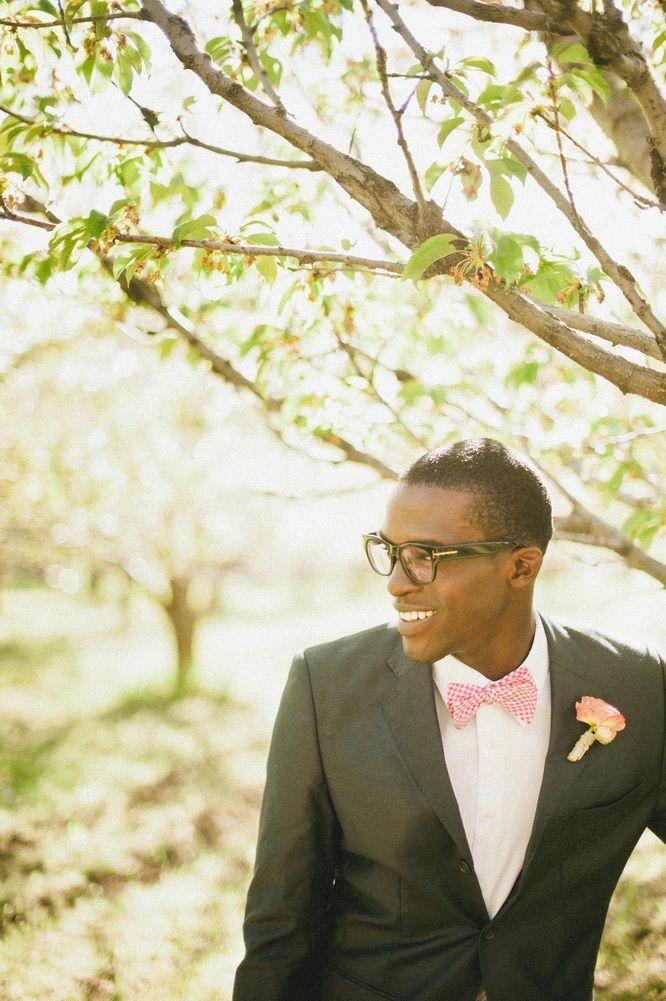 Noivo negro com terno cinza escuro, gravata borboleta xadrez vermelha, flor na…