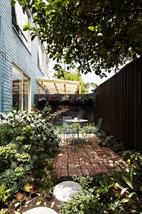 Small side garden with brick patio and outdoor dining table