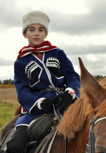 A Russian girl in the traditional Cossack's costume is riding a horse.