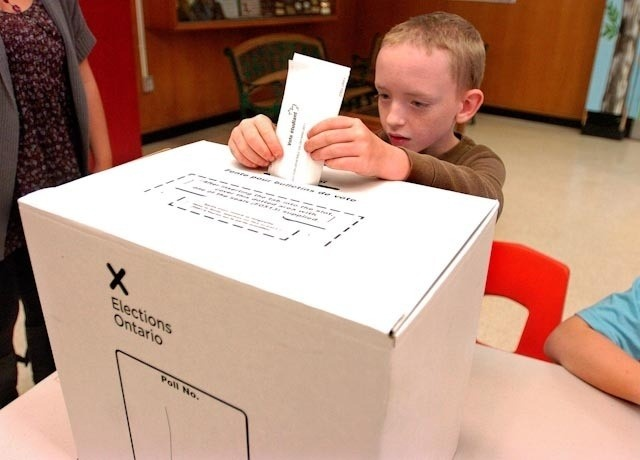 Polling clerk Zackary Heppenheimer, 9, placed a ballot in the box during the Student Vote held at Prince Charles public school on Wednesday October 5, 2011 in London, Ont.