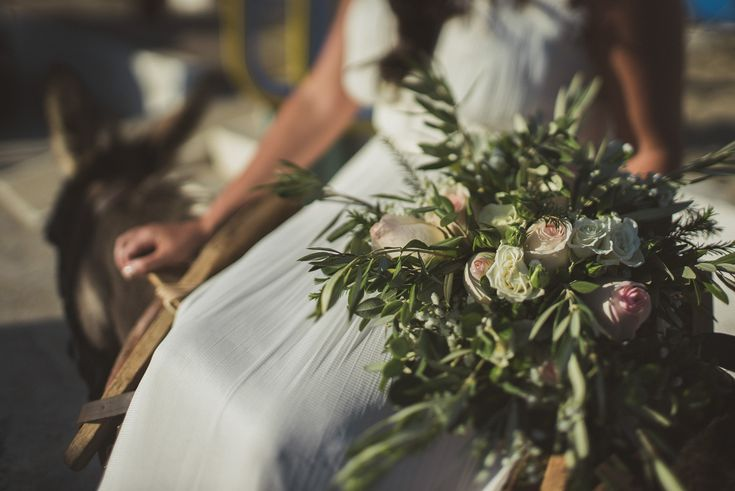 Jewish – Greek wedding on the beach in Chania Crete, Greece – love the light blog by Andreas Markakis Photography in Chania Crete Greece  Bride with bouquet arriving on a donkey