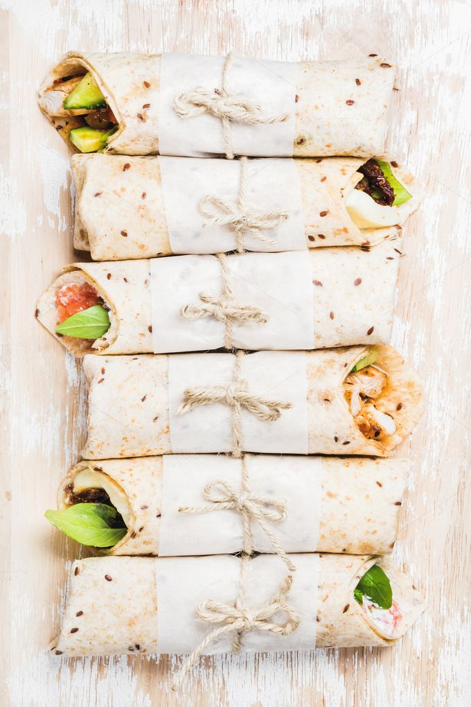 #Tortilla wraps with various fillings  Tortilla wraps with various fillings on shabby white painted wooden background top view horizontal composition. Healthy snack or take-away lunch bites