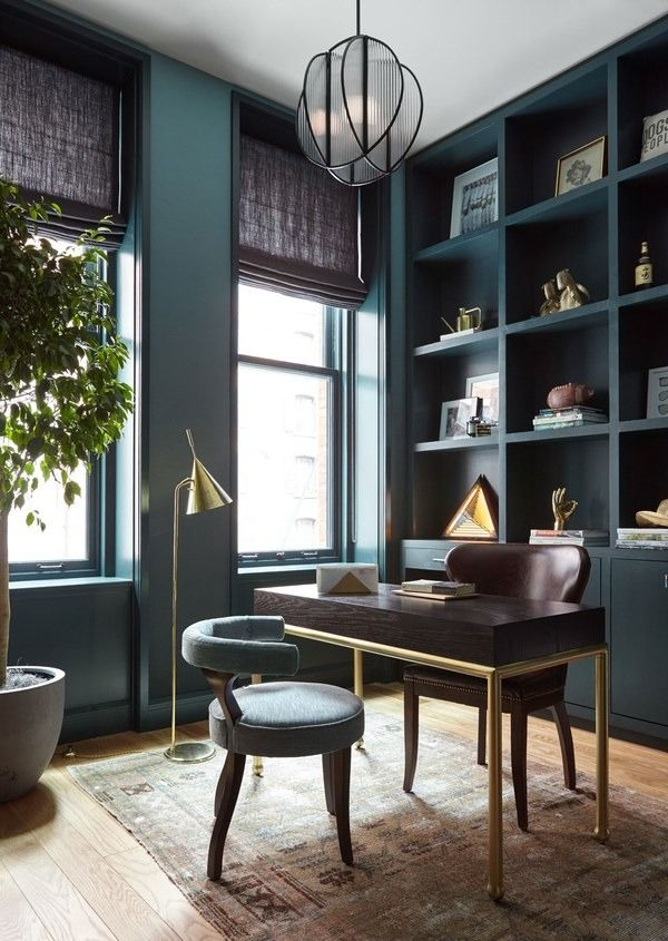 The designers transformed the apartment's third bedroom into a home office with custom built-ins. The walls boast a jade-toned wallcovering from Calico Wallpaper | archdigest.com