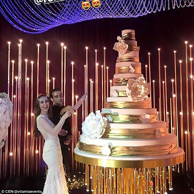 The groom Gaspar, 29, seen cutting the towering cake with his new bride, is the son of Rus...