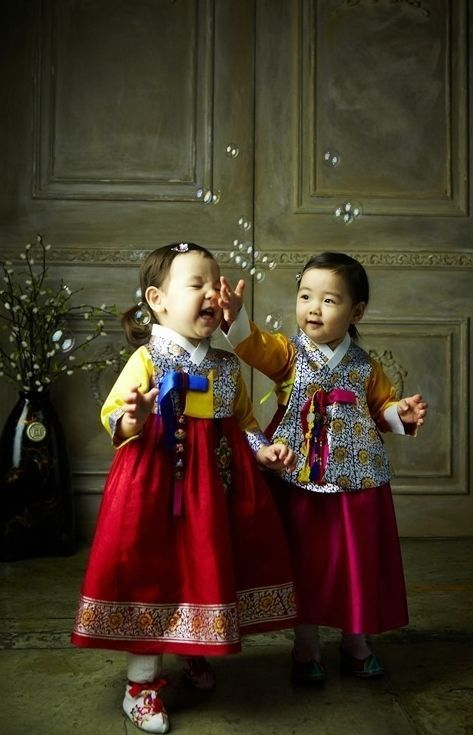 Little girls in hanbok playing with bubbles.