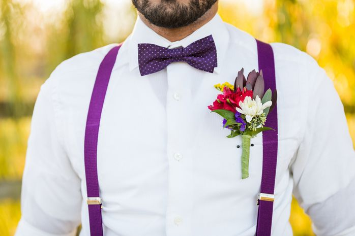 Unique groom outfit idea - groom in bright purple suspenders, purple polka dot bowtie, and fun + colorful boutonniere {Greystone Riding Academy}