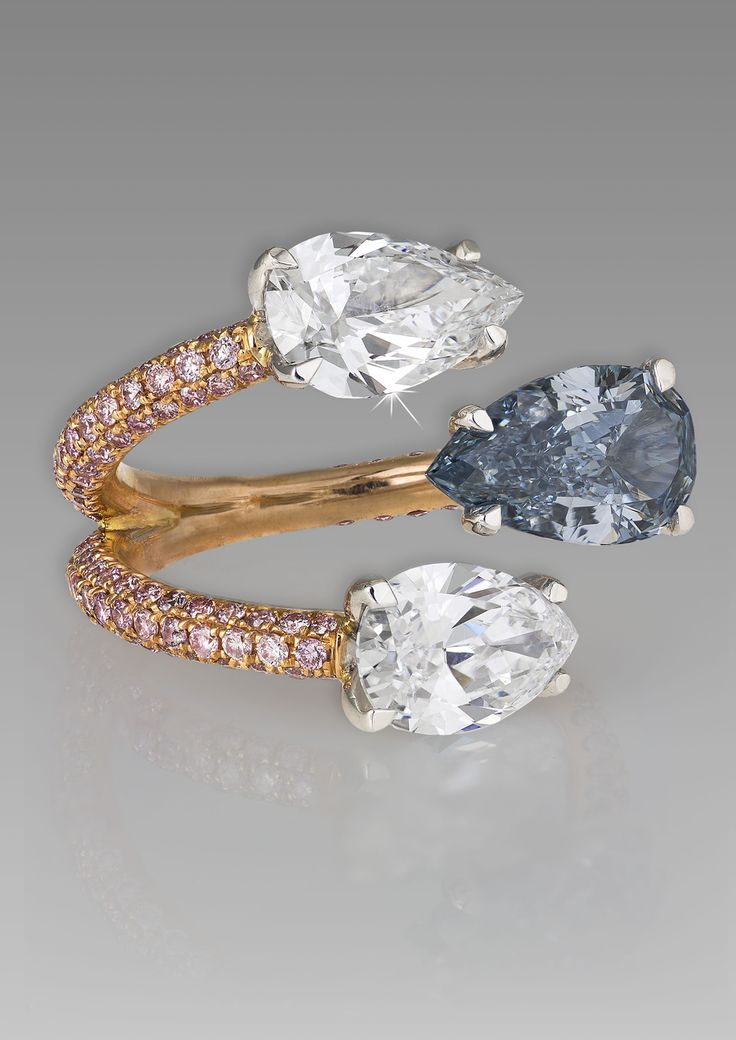 A unique DavidMorris bluediamond engagementring featuring a rose gold and melée diamond band that separates to meet two pear-shaped white diamonds and one pear-shaped blue diamond.