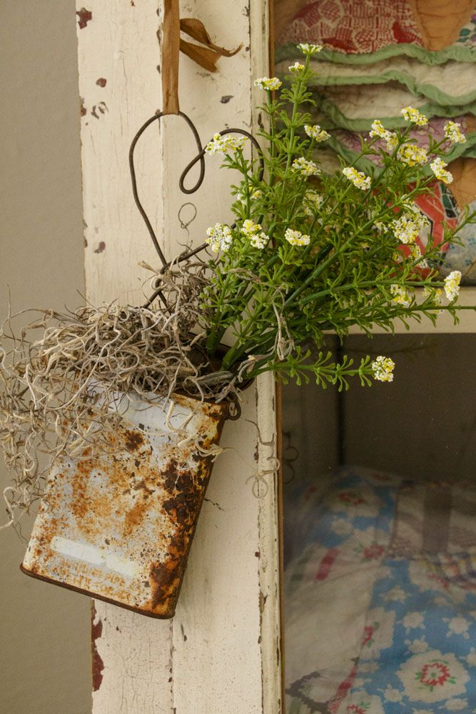 A rusty tin filled with moss and wildflowers with a heart-shaped wire handle is perfect for dangling from a cabinet knob or pull.