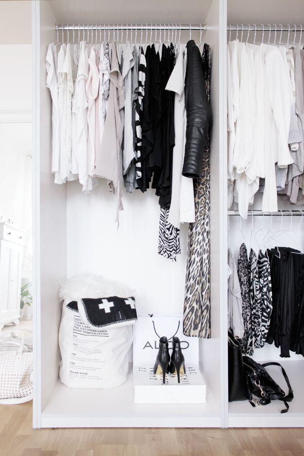 Een open kast met kledingrekken