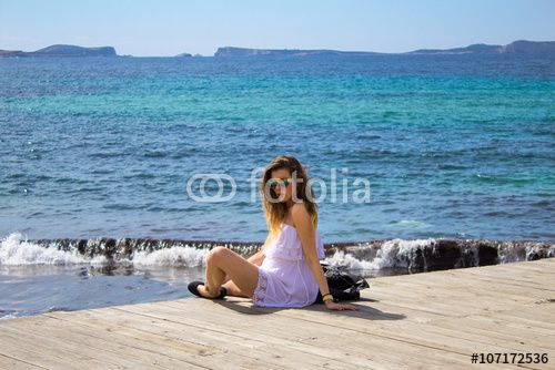 Fit girl sitting on the beautiful pier at the seaside with waves