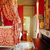 Champ de Bataille -- The guest bedroom is dominated by a lit a la polonaise with pretty red and white floral bed hangings