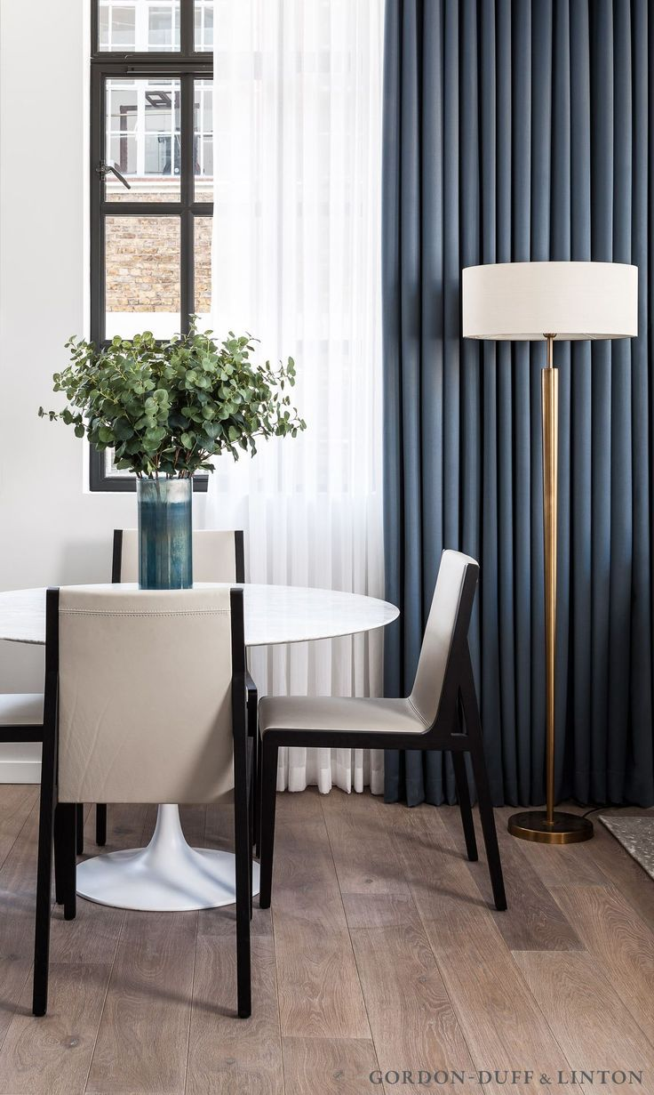 Dining area with Saarinen marble table and two-tone dark wood and leather chairs.