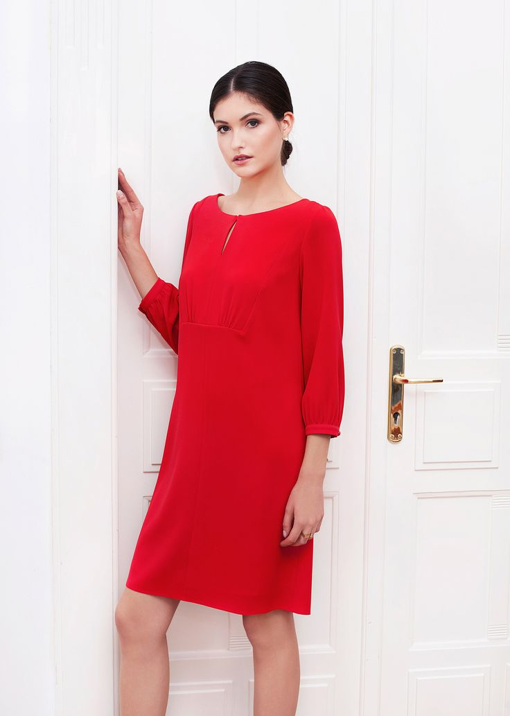 Nicole dress red. The simple flared line is embellished by gentle folds and beautifully rounded neckline with teardrop fastening. The material displays rich colour and light, fluid texture, defining the effortlessly chic silhouette.