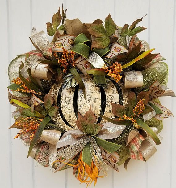 """This beautiful fall wreath is elegant in its design, and subtle in its colors, which makes for the perfect seasonal wreath! The wreath is made of a variety of fall leaves, grasses, and greenery to complement fall flowers, all sitting on a bed of deco mesh. A fluff of orange feathers reaches out from the bottom of the wreath for color. Several wired fall ribbons in 1 ½ and 2"""" widths give the wreath a splash of presentation. A large gold metal pumpkin—keeping within the color theme and…"""
