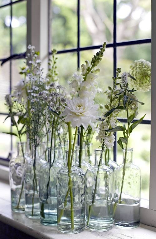 A collection of white flowers from the garden arranged in matching bottles. Light and fresh for spring.