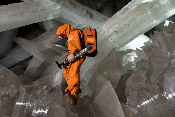 The Cave of Crystals near Chihuahua, Mexico.     Those giant crystals of gypsum (CaSO4) probably grew to their massive size really slowly in a bath of hot water and dissolved minerals. Now that the water has been pumped out by industrial miners, scientists are free to explore…with the help of some ice-cooled orange jumpsuits: The caves average a termperature of 118 F, and 90 % humidity.