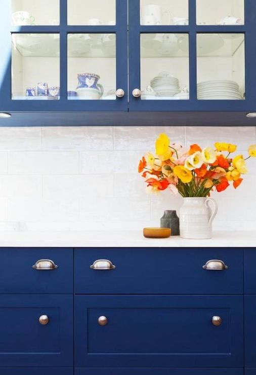 Amazing kitchen with cobalt blue cabinets, marble countertops, glossy white glass subway tiles backsplash and brushed nickel hardware.
