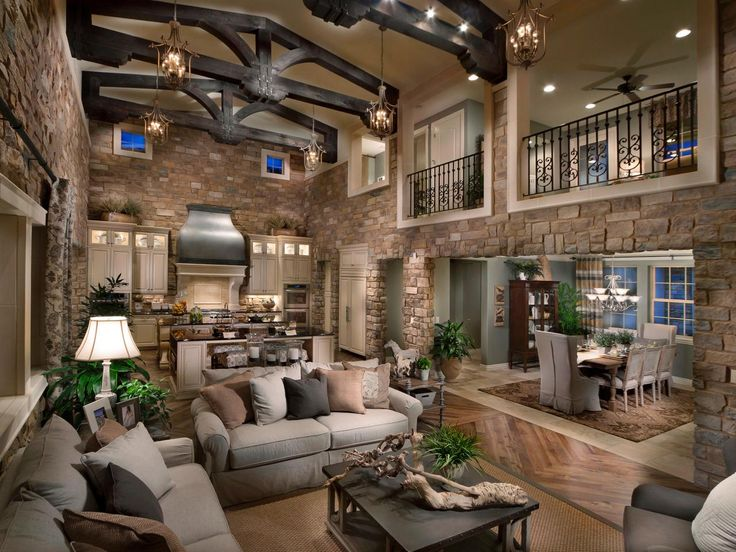 This rustic living room and kitchen is a magnificent space that has stone walls and vaulted ceiling.