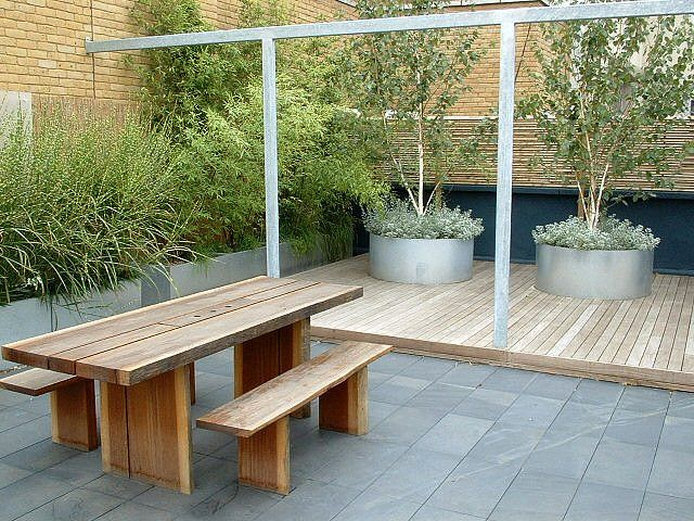 contemporary roof garden by modular. Slate paving and hardwood decking  create a wonderful space for dining and entertaining. Planters contain multi-stemmed Silver Birch trees, grasses and bamboos.