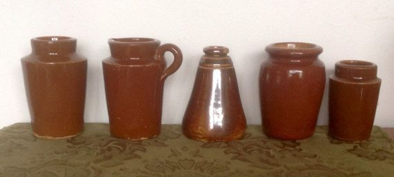 A varied set of five of the more unusual shaped stoneware pots from the late 1800s or early 1900s...all in a dark brown earth tone glaze.  All measure between 3 and 4 tall. They have the usual changes in glaze colour, rough spots etc. The jug has a pale streak at the back ( see photo 3 ) The smallest pot has one tiny chip in the glaze at the base.  Generally all in very good vintage condition. A nice addition to a country kitchen.