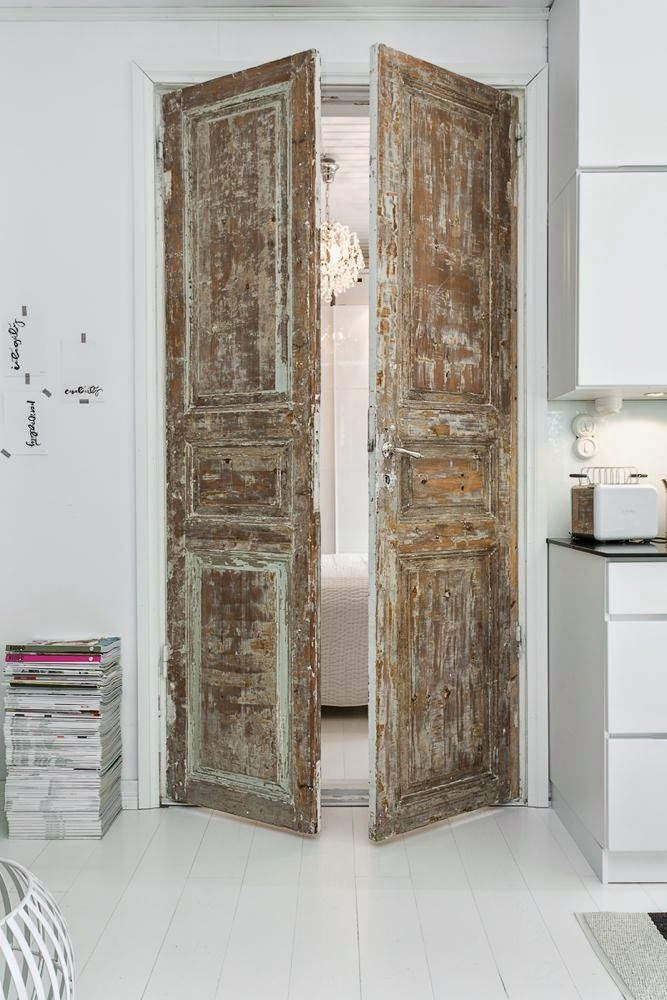 These wooden doors are antiqued to perfection. They add a rustic, shabby chic feel to this modern style, all white living space.