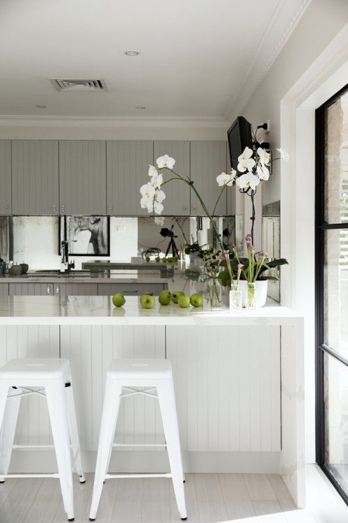 """Sneak Peek: A Sophisticated Australian Home. """"The kitchen has recently been redesigned and 'squared up'... The counter tops are by Quantum Quartz and Calacatta quartz with panelled cupboards in a Zeus Lunar grey matt at 50%. The backsplash is a mirror that has been made to look vintage and my favourite detail are the glass knobs which look like the top of the Chanel perfume bottle from Mother of Pearl and Sons."""" #sneakpeek"""