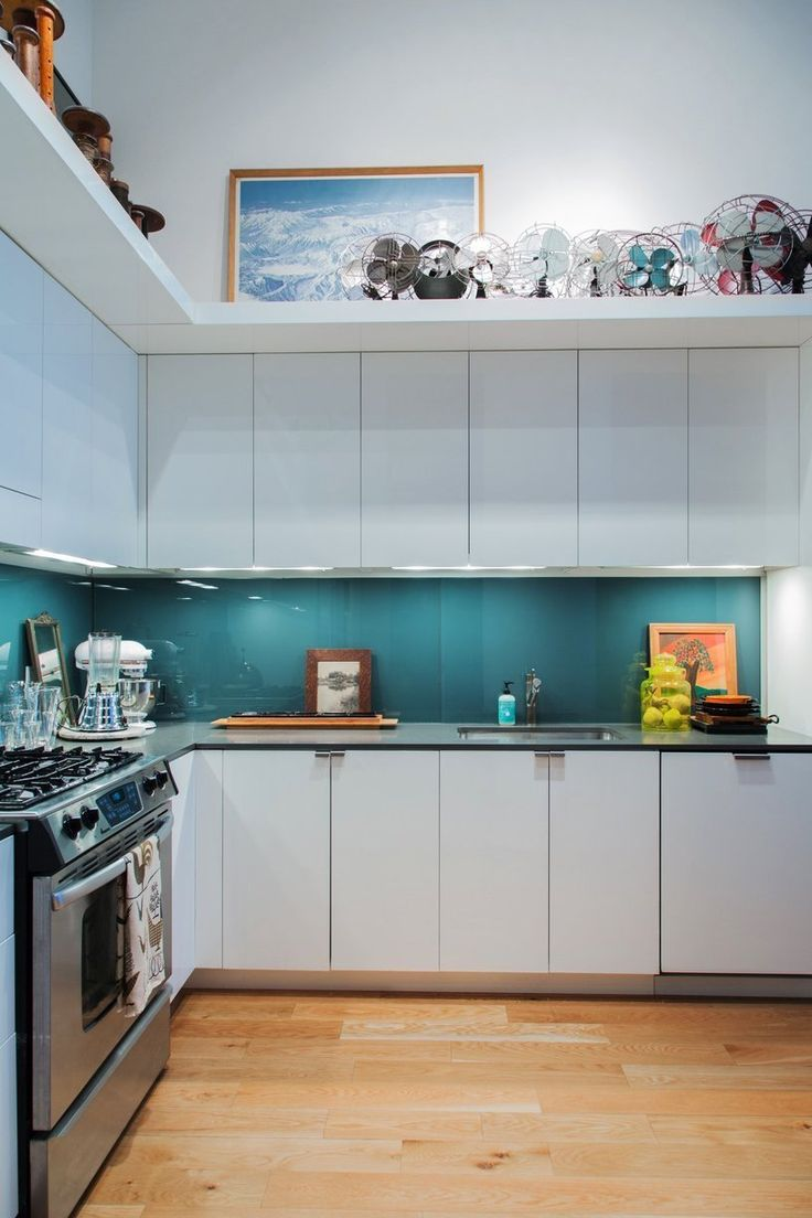 I love the glass back-splash and thin dark counter tops with the shelf above.  Other pictures in this tour show that it makes the kitchen cozy while not diminishing the volume of space.