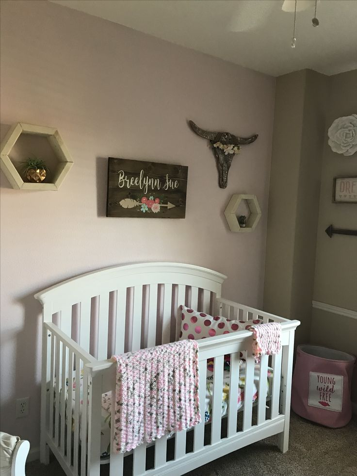 Rustic Baby Girl Nursery Decor. Wild & free theme complete with cow skulls and floral crowns. Light pink and gold accents     #hobbylobby #bohochic #rusticdecor #babygirl #nursery #hexagonshelves #crib #floralcrowns #arrow #floral