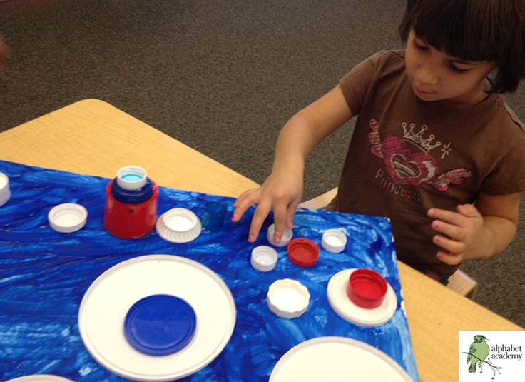 A Patriot's Day (or 4th of July) collage! We began by collaboratively painting a large piece of cardboard blue. After the paint dried, the children glued red, white and blue bottle caps and tops from containers onto it.  — Alphabet Academy North Preschool  http://thealphabetacademy.com  #reggio-inspired #patriotic #holidays #paint #glue #lids #caps #preschool