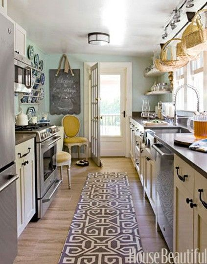 Galley Kitchen With Cream Cabinets And Blue Wall Stainless Steel Appliances