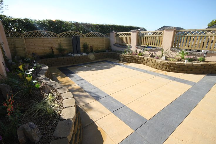 Sandstone Yellow Paving with Black Border. Raised Flower Beds with a Water Feature at the Back