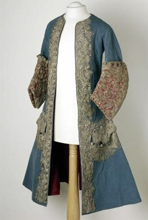 """Kaftan of Emperor Peter II, made in France, circa 1727-1730.  The kaftan is made of blue cloth embroidered with threads of silver. The double-breasted knee-length coat is close-fitting the chest and is widening from the waist to the hem.  The deep, curved cuffs, lined with crimson silk, are the """"boot-cuff"""" sleeves, which were in fashion from 1725 to 1735. The laps, cuffs and side slits are ornamented with floral"""