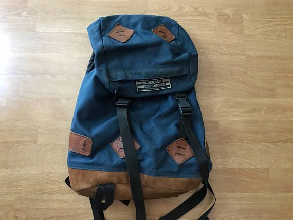 Vintage blue canvas wilderness experience backpack. Brown suede leather bottom with leather lashing squares on top, front, and sides. Great vintage backpack look. Marked wilderness experience chatsworth California. See below for condition details. Measures approximately 18 x 15 x 7 Marked wilderness experience chatsworth California Vintage condition- has marks, scratches, scuffs all over, back lower area has a large burn hole, priced accordingly, could possibly be patched with some nylon…