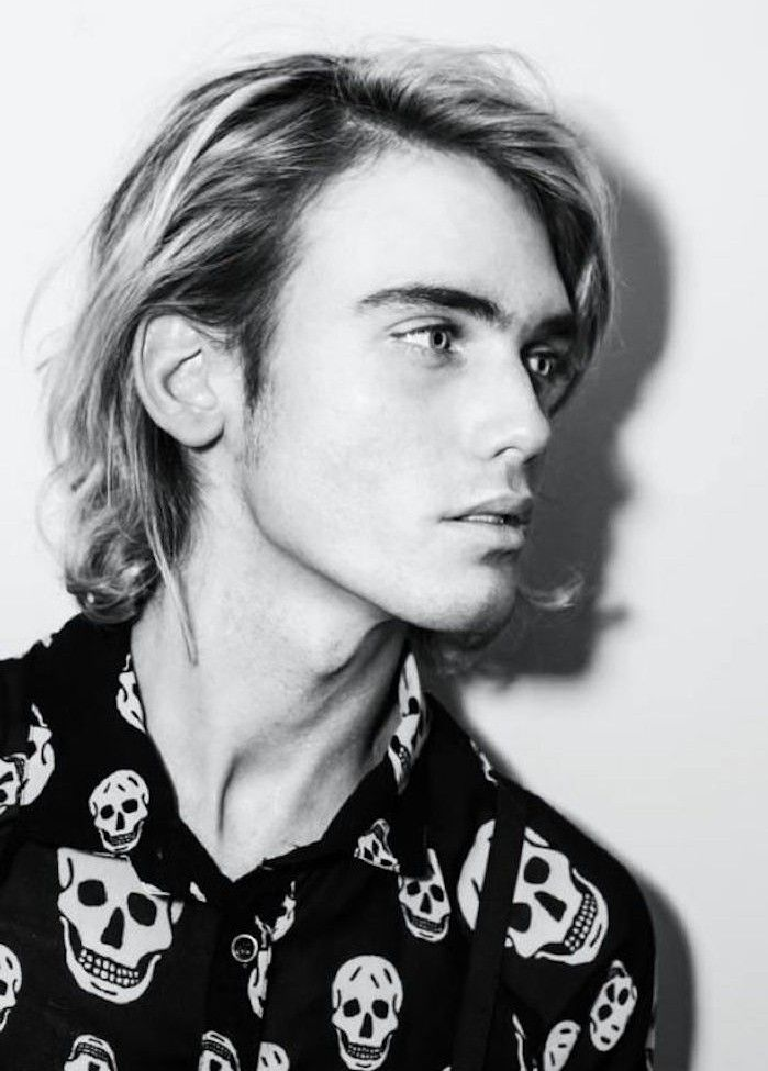 medium length hairstyles, young man with blonde hair, side parted and messy, tucked behind ear