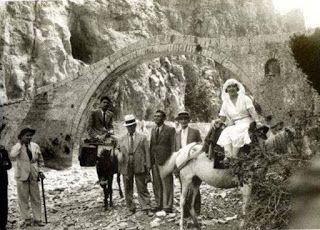 """Η νύφη στη φάση της """"διάβασης"""" προς το χωριό του γαμπρού μετά τη στέψη, σε έναν τόπο, κάτω από γεφύρι,  που ορίζει εδώ συμβολικά όσο και τοπικά τη διαβατήρια  """"γέφυρα"""" και το """"πέρασμα""""  ποταμού. Αρχείο  Δημητρίου Σαλαμαγκα από το λεύκωμα του Ριζαρειου Ιδρύματος """"ΖΑΓΟΡΙΣΙΩΝ ΒΙΟΣ"""", 2003. Η φωτογραφία είναι της δεκαετίας 1930 και απεικονίζεται το γεφύρι του Κόκκορου,  στο Ζαγόρι Ηπείρου)"""