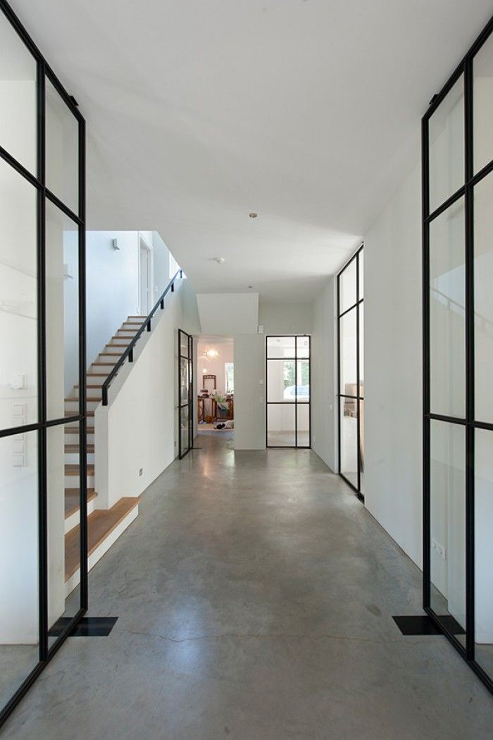 Black French casement pivot doors, concrete floors, wood tread stairs