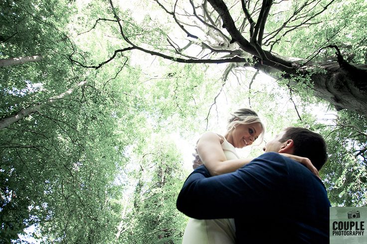 The groom lifts his bride in the beautiful woods outside the Summerhouse Hotel. Wedding at Summerhill House Hotel by Couple Photography.