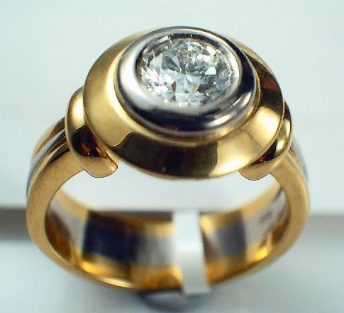 Something a little more solid with a half carat round brilliant cut diamond in a two tone band.